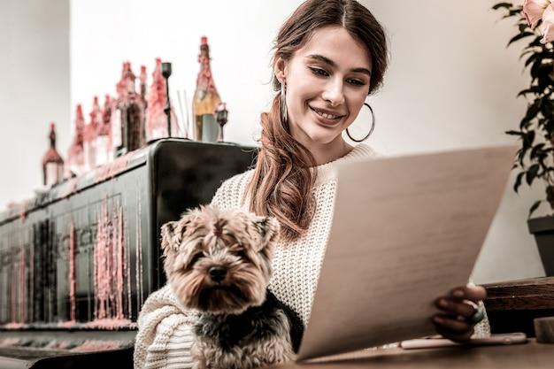 Spojrzenie na menu. kobieta z psem w rękach uważnie czytająca menu
