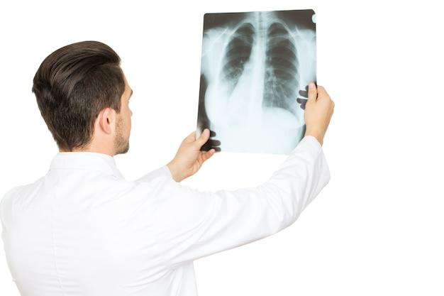 Spojrzenie na twój problem. profesjonalny lekarz przeprowadzający badanie rentgenowskie na białym tle na białym tle z boku