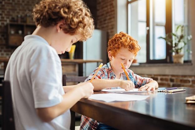 Spokój i spokój. selektywne skupienie się na inteligentnym małym rudowłosym chłopcu siedzącym obok swojego brata i skupiającym się na kartce papieru podczas rysowania.