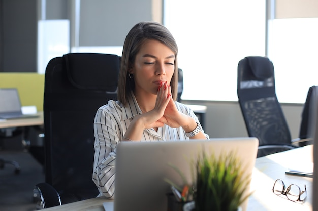 Spokój piękna kobieta medytuje w biurze z zamkniętymi oczami.