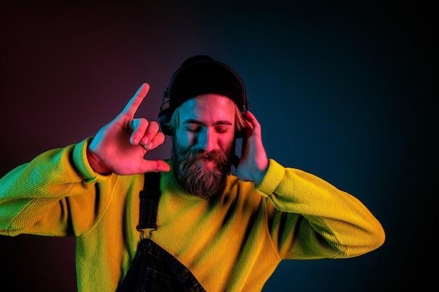 Spokój, radość. portret mężczyzny rasy kaukaskiej na tle gradientu studio w świetle neonu. piękny męski model w stylu hipster w słuchawkach. pojęcie ludzkich emocji, wyraz twarzy, sprzedaż, reklama.