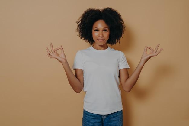 Spokojna afroamerykańska młoda kobieta trzymająca ręce w geście mudry, odizolowana na beżowej ścianie