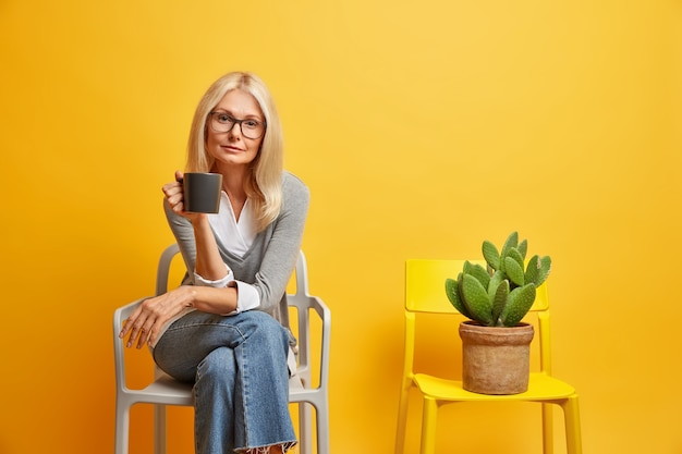 Spokojna blondynka siedzi na wygodnym fotelu z napojem, wygląda pewnie i pozuje w pobliżu kaktusa doniczkowego, ciesząc się spokojną atmosferą. koncepcja stylu życia