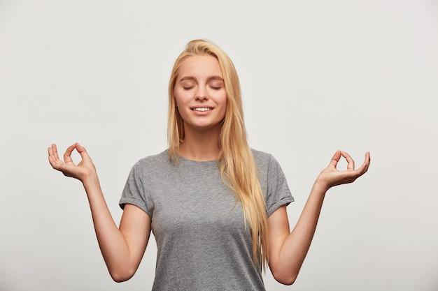 Spokojna blondynka uśmiecha się lekko, medytując próbuje się zrelaksować, koncentruje się na czymś
