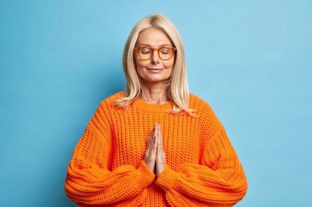 Spokojna blondynka z zamkniętymi oczami stoi w pozie do modlitwy, modli się o dobre samopoczucie ubrana w dzianinowy sweter i okulary.