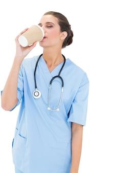 Spokojna, brązowowłosa pielęgniarka w niebieskich szortach, ciesząc się swoją kawą