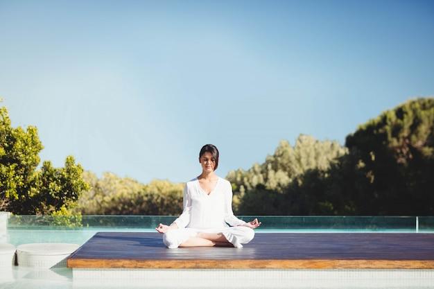 Spokojna brunetka robi joga przy basenem