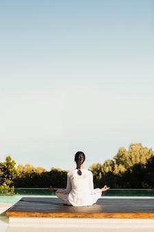 Spokojna brunetka robi joga przy basenie