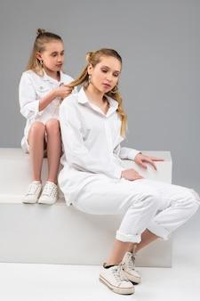 Spokojna, długowłosa dziewczynka siedzi za starszą siostrą i robi nową fryzurę