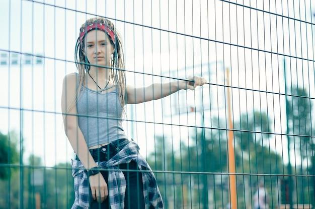 Spokojna długowłosa młoda kobieta ubrana w zwykłe ubrania i patrząc na ciebie, dotykając ogrodzenia ogniwa łańcucha