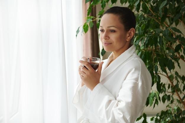 Spokojna dojrzała kobieta w białej szacie stoi z filiżanką kawy w dłoniach