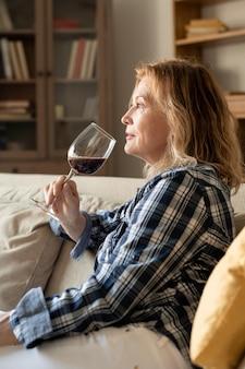 Spokojna dojrzała kobieta w codziennym stroju, popijająca kieliszek czerwonego wina, siedząc na kanapie w domu i ciesząc się odpoczynkiem wieczorem