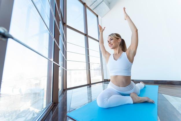 Spokojna dziewczyna robi joga, siedząc w pozie gołębia z podniesionymi rękami