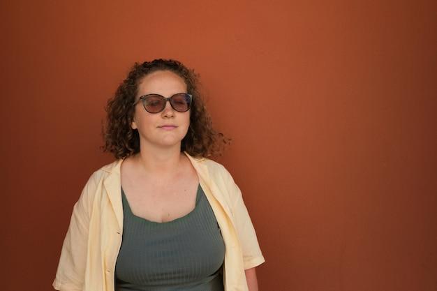 Spokojna dziewczyna stoi na pomarańczowym tle z zamkniętymi oczami w okularach przeciwsłonecznych kobieta z kręconymi włosami