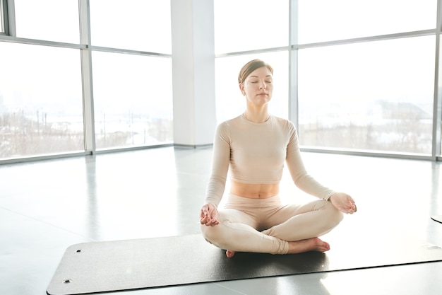 Spokojna dziewczyna w lekkiej odzieży sportowej siedzi na macie ze skrzyżowanymi nogami podczas ćwiczeń relaksacyjnych