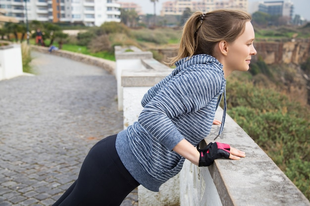 Spokojna dziewczynka fit robi poręcze push up