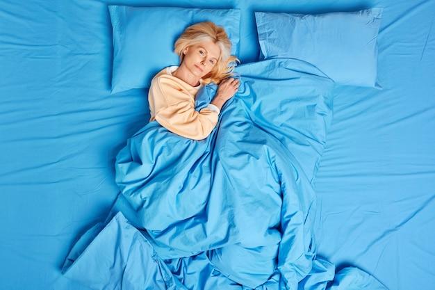 Spokojna europejka w średnim wieku budzi się zadowolona po zobaczeniu dobrych snów w pozach dobrze wyspanych pod niebieskim kocem, ubrana w piżamę, czuje się komfortowo, cieszy się leniwym dniem. czas na sen i przytulny poranek