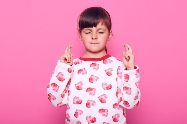 Spokojna i skoncentrowana dziewczynka stojąca z zamkniętymi oczami i skrzyżowanymi palcami, myśląca o spełnieniu swojego marzenia, ubrana w swobodny sweter, odizolowana na różowej ścianie