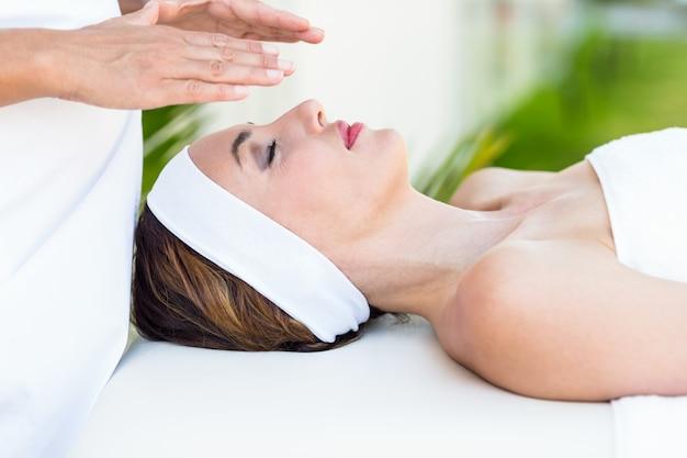 Spokojna kobieta otrzymująca leczenie reiki