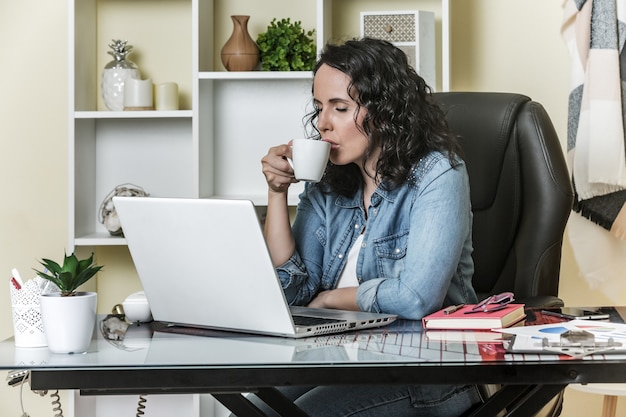 Spokojna kobieta pije gorącą kawę podczas gdy używać laptop w domu