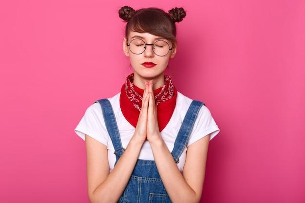 Spokojna kobieta rasy białej trzyma oczy zamknięte, modli się stojąc przy różowej ścianie, prosi boga o coś ważnego, nosi białą koszulkę, dżinsowy kombinezon, chustę na szyi i okulary.
