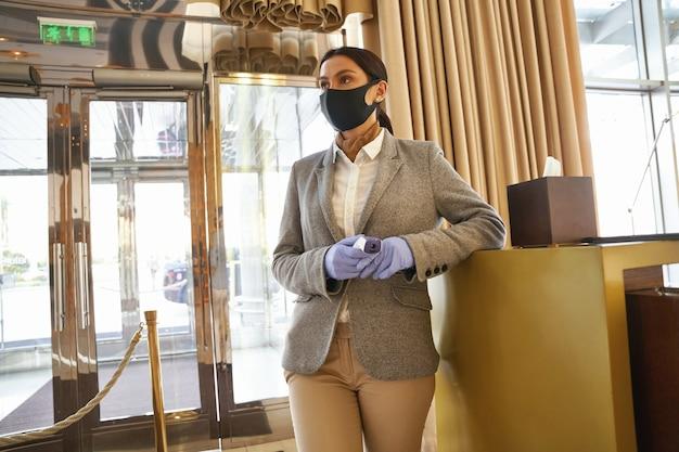 Spokojna kobieta w masce medycznej i gumowych rękawiczkach stoi z termometrem na podczerwień w dłoniach