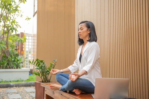 Spokojna kobieta z zamkniętymi oczami praktykuje jogę w pozycji lotosu