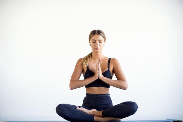 Spokojna ładna kobieta robi ćwiczenia jogi na białym tle.
