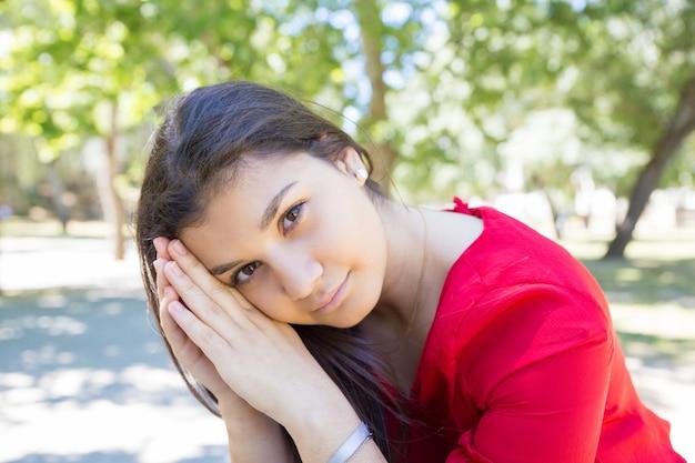 Spokojna ładna młoda kobieta relaksuje i pozuje przy kamerą w parku