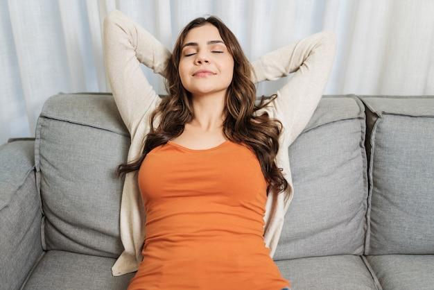 Spokojna latynoska kobieta relaksuje się na miękkiej i wygodnej sofie, ciesząc się bezstresowo na kanapie