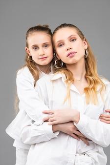 Spokojna mała dziewczynka mocno przytula swoją atrakcyjną starszą siostrę, stojąc z tyłu