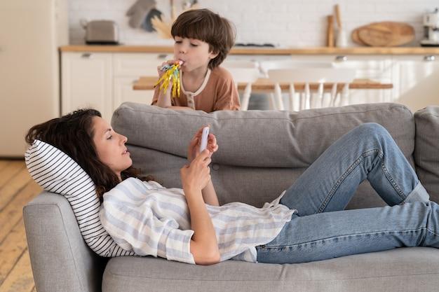 Spokojna mama leżąca na kanapie ze smartfonem odwrócona od hałaśliwego, głośnego, złego zachowania syna, przyciągającego uwagę