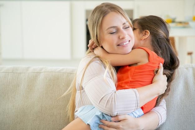 Spokojna mama trzyma swoją małą dziewczynkę na kolanach i przytula ją.