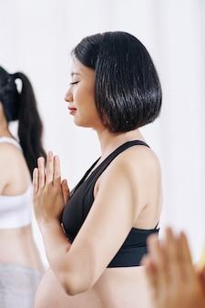 Spokojna młoda azjatycka kobieta w ciąży z rękami w geście namaste medytacji w klubie fitness