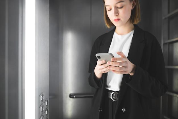 Spokojna młoda bizneswoman w eleganckim garniturze patrzy na swojego smartfona w windzie.