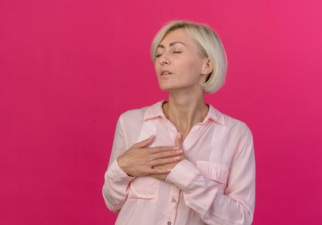 Spokojna młoda blond słowiańska kobieta trzymając ręce na klatce piersiowej z zamkniętymi oczami na białym tle na różowym tle z miejsca na kopię