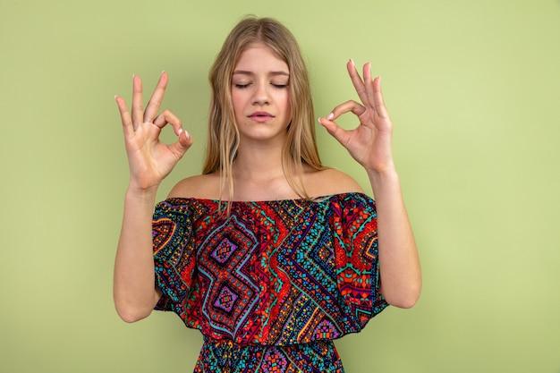 Spokojna młoda blondynka słowiańska stojąca z zamkniętymi oczami i medytująca