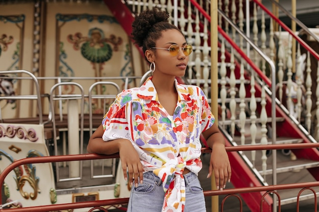 Spokojna młoda brunetka kręcona kobieta w dżinsowych spodniach, kolorowej bluzce i pomarańczowych okularach przeciwsłonecznych odwraca wzrok i opiera się na karuzeli na zewnątrz
