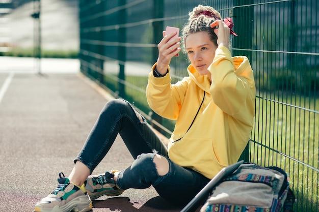 Spokojna młoda dama ubrana w zwykły strój i patrząc na swoje odbicie w lustrze na boisku sportowym