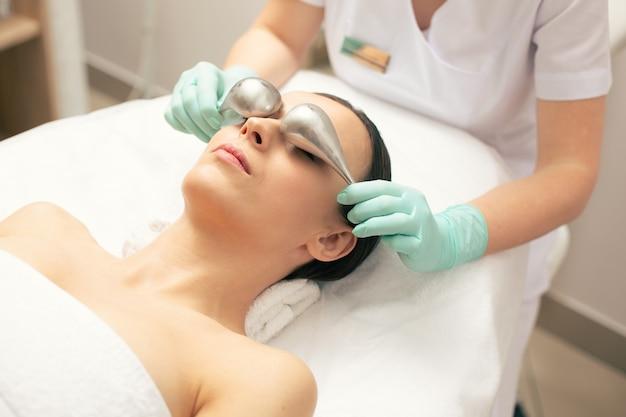 Spokojna młoda kobieta leżąca na kanapie lekarskiej i profesjonalna kosmetolog używająca krio-kija podczas zabiegu