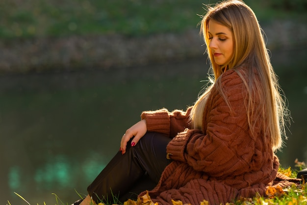 Spokojna młoda kobieta relaks w wieczornym świetle siedząc na trawie nad stawem w jesiennym parku podświetlanym przez złote słońce