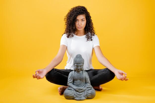 Spokojna młoda murzynka medytuje joga i buddha z buddha odizolowywał nad kolorem żółtym