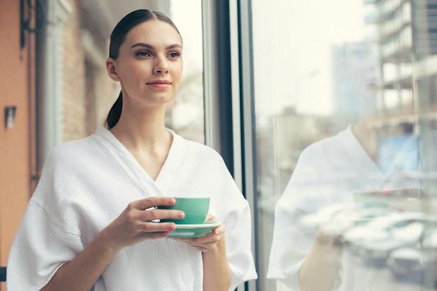 Spokojna młoda piękna dama w białym szlafroku z namysłem patrząca w dal i uśmiechnięta stojąc przy oknie z filiżanką herbaty w dłoniach