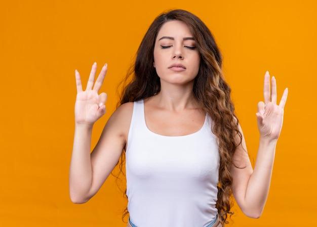 Spokojna młoda piękna dziewczyna medytuje z zamkniętymi oczami na odizolowanej pomarańczowej przestrzeni