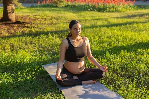 Spokojna młoda pozytywna kobieta w ciąży w kostiumie gimnastycznym ćwiczy jogę i medytuje na macie