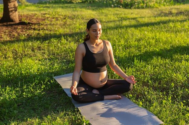 Spokojna młoda pozytywna kobieta w ciąży w kostiumie gimnastycznym ćwiczy jogę i medytuje siedząc na macie