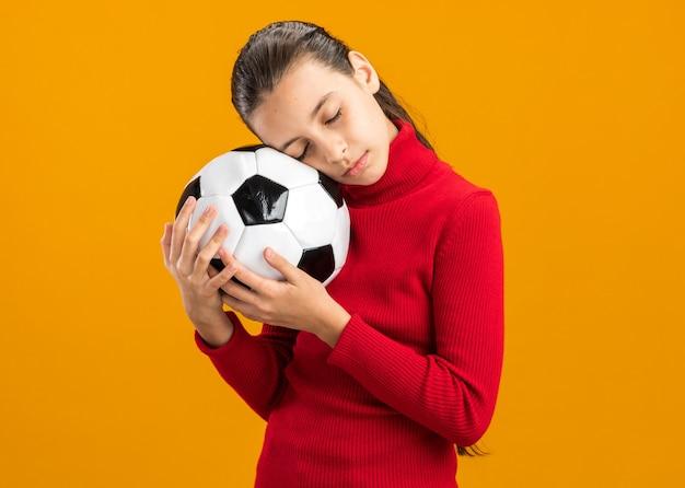 Spokojna nastolatka stojąca w widoku z profilu, trzymająca piłkę nożną opartą o głowę z zamkniętymi oczami, odizolowana na pomarańczowej ścianie z miejscem na kopię