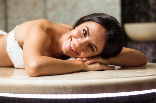 Spokojna piękna młoda brunetka o szczupłym ciele i zdrowej skórze odpoczywa i wykonuje zabiegi spa w łaźni tureckiej lub hammamie