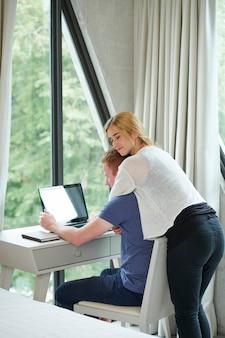 Spokojna Piękna Młoda Kobieta Przytula Chłopaka Lub Męża Kodującego Na Laptopie W Domowym Biurze Premium Zdjęcia