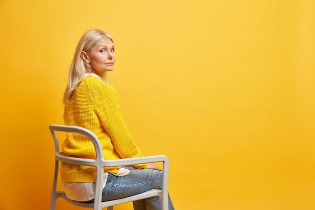 Spokojna piękna pięćdziesięcioletnia kobieta siedzi na krześle będąc sama myśli o życiu nosi żółty sweter z dzianiny i dżinsy puste miejsce na kopię